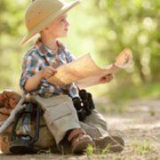 ילד יושב על תיק עם מפה ביד