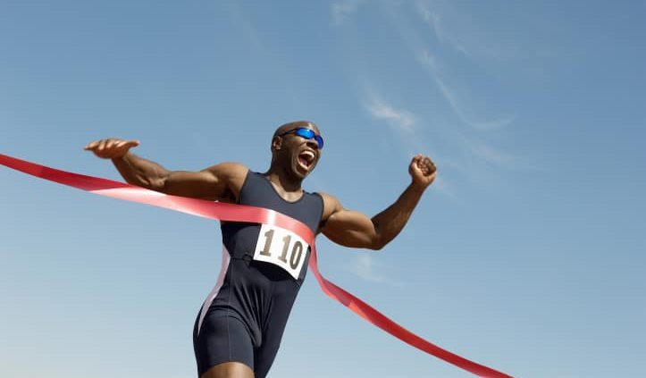 Low angle view of an African American male runner winning race a
