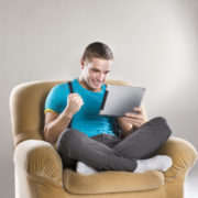 Handsome young man with tablet sitting in sofa